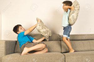 29937270-I-bambini-che-combattono-insieme-con-cuscini-sul-divano-a-casa-Archivio-Fotografico
